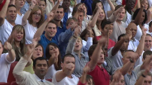 vidéos et rushes de ms pan spectators in bleachers cheering, london, uk - acclamation de joie