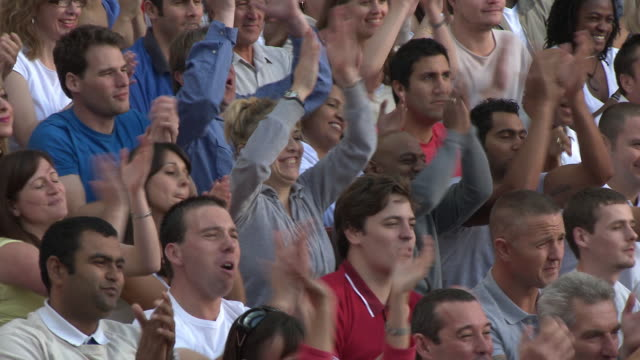 ms pan spectators in bleachers cheering, london, uk - spettatore video stock e b–roll