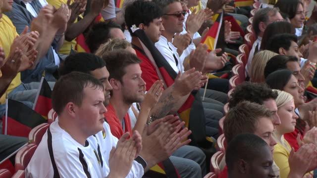 MS PAN Spectators in bleachers clapping and waving German flags, London, UK