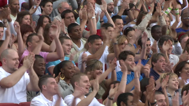ms spectators in bleachers clapping hands, london, uk - stadio video stock e b–roll