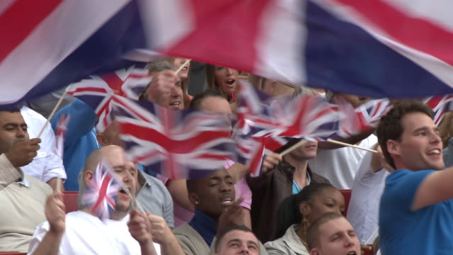 ms pan spectators in bleachers waving british flags, london, uk - british culture stock videos & royalty-free footage
