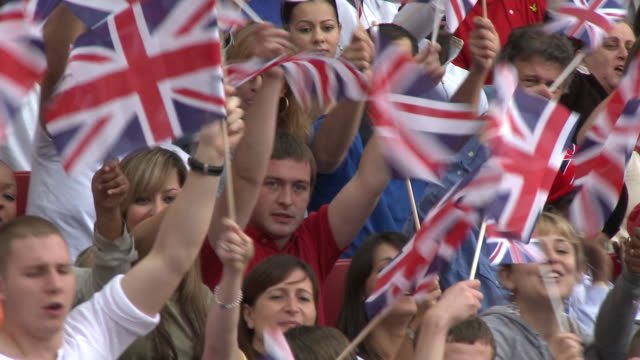 vidéos et rushes de cu pan spectators in bleachers waving british flags, london, uk - angleterre