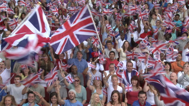 WS Spectators in bleachers waving British flags, London, UK
