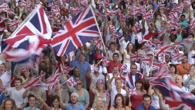 ws spectators in bleachers waving british flags, london, uk - brittiska flaggan bildbanksvideor och videomaterial från bakom kulisserna