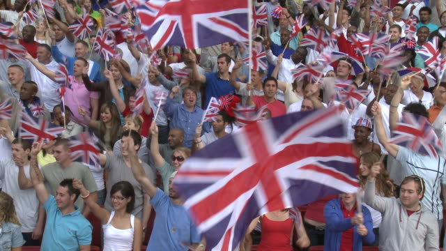 vídeos de stock, filmes e b-roll de ws spectators in bleachers waving british flags, london, uk - reino unido