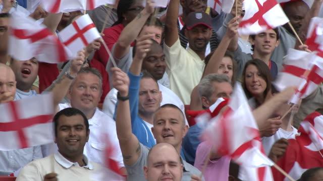 ms pan spectators in bleachers waving english flags, london, uk - bandiera inglese video stock e b–roll