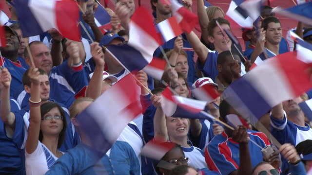 stockvideo's en b-roll-footage met ms pan spectators in bleachers waving french flags, london, uk - franse cultuur
