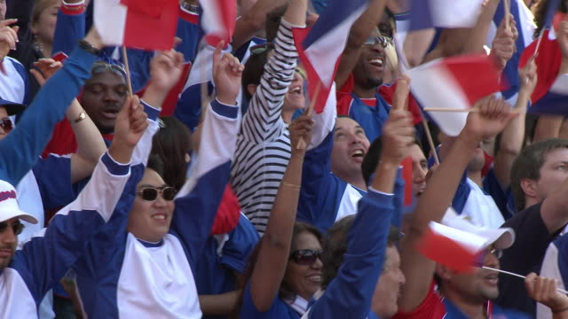 vidéos et rushes de ms pan spectators in bleachers waving french flags, london, uk - support