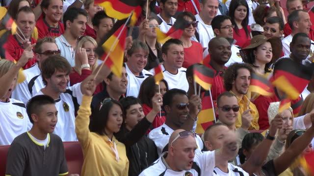 MS Spectators in bleachers waving German flags, London, UK