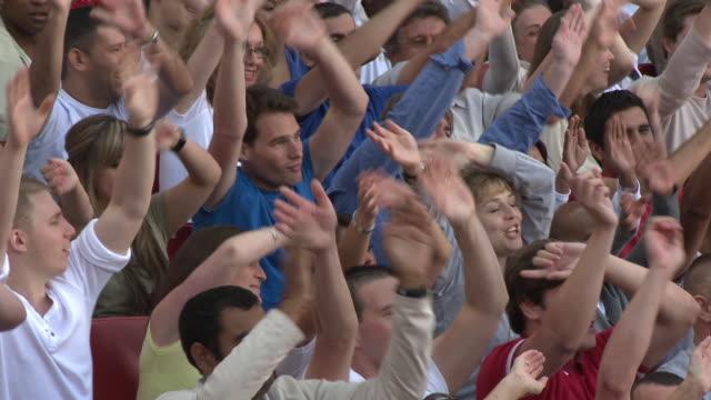 MS ZO PAN Spectators in bleachers waving hands, London, UK