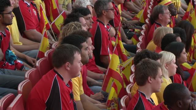 ms pan spectators in bleachers waving spanish flags, london, uk - スペイン国旗点の映像素材/bロール