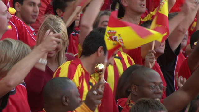 cu pan spectators in bleachers waving spanish flags, london, uk - スペイン点の映像素材/bロール