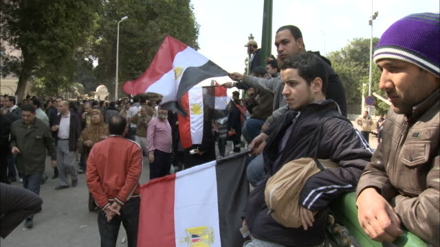 pan spectators leaning on railing holding egyptian flags as pedestrians are walking through the streets / cairo egypt - 2011 stock videos & royalty-free footage