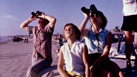 vídeos y material grabado en eventos de stock de spectators looking through binoculars and telescopes, eagerly awaiting mercury atlas 6 launch / television camera crews covering the event / banner... - ubicaciones geográficas