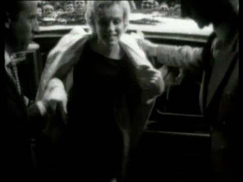 stockvideo's en b-roll-footage met spectators on street/ ms young men on street/ ms marilyn monroe getting out of car/ marilyn monroe and husband arthur miller arriving for press... - marilyn monroe