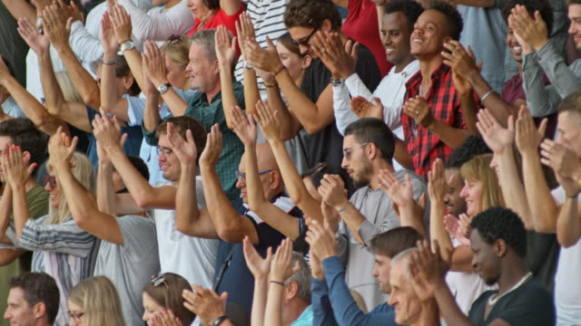 slo mo spectators on the stadium clapping their hands standing up - fan enthusiast stock videos & royalty-free footage
