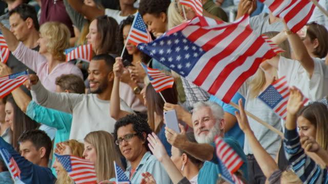 SLO MO Spectators on the stadium tribune waving American flags