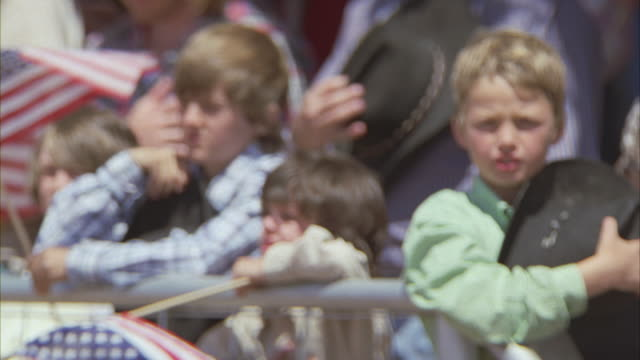 Spectators singing the Star Spangled Banner at a rodeo.