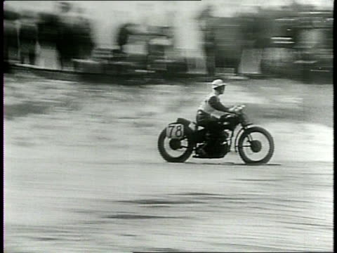 spectators stand in front of cars as derby racers speed past / several riders race around a corner on a dirt track / rider crashes off of his bike /... - narrating stock-videos und b-roll-filmmaterial