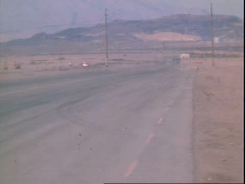 spectators standing, leaning against chain link fence / red ford station wagon driving away from camera, dusty desert road / front engine-mounted top... - nevada stock-videos und b-roll-filmmaterial