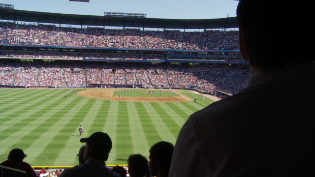 spectators watch a baseball game in a stadium. - baseball diamond stock videos & royalty-free footage