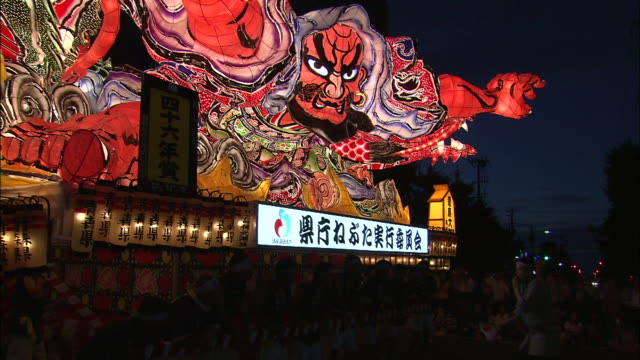 spectators watch a colorful float pass during the nebuta festival. - 伝統的な祭り点の映像素材/bロール