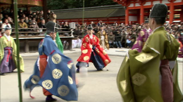 Spectators watch a game of kemari in the inner courts of Shimogamo Shrine.