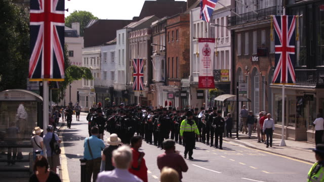 spectators watch a military band march down high street in windsor, england. - music or celebrities or fashion or film industry or film premiere or youth culture or novelty item or vacations stock videos & royalty-free footage