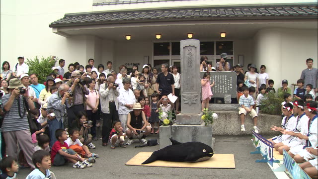 spectators watch as a chorus of boys performs at a japanese whale festival. - cultures stock videos & royalty-free footage