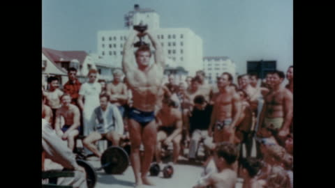 1947 spectators watch as man works out at muscle beach - ベニスビーチ点の映像素材/bロール