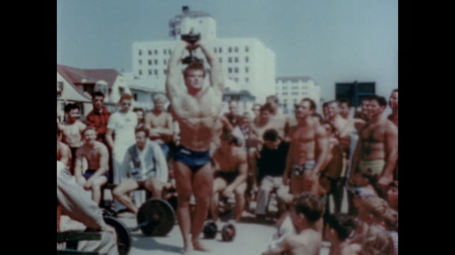 vídeos de stock e filmes b-roll de 1947 spectators watch as man works out at muscle beach - 1947