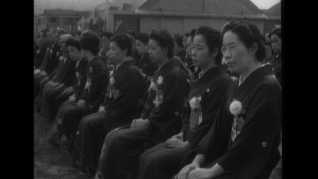 Spectators watch as Navy Minister Koshiro Oikawa and Army Minister Hideki Tojo make comments as 51 type 97 fighters are put into service at Haneda...