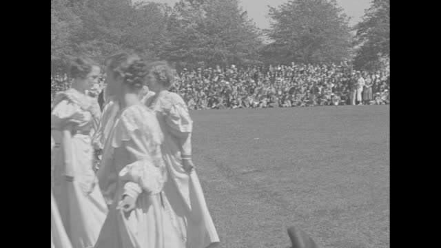 WS spectators watch as Old English pageant festivities continue at Beaver College outdoor event features a background of 'buildings' and a 'throne' /...