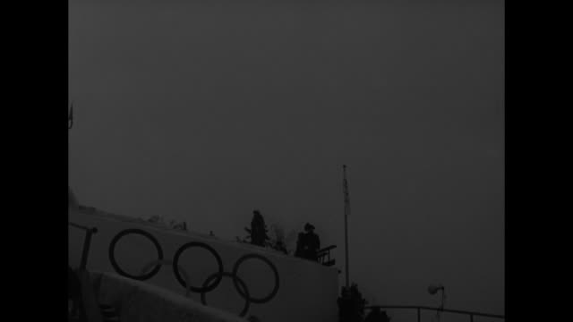 spectators watch as one after another olympians sail through the air for the ski jump at the holmenkollen ski jump / someone being carried off the... - nordic skiing event stock videos and b-roll footage