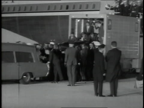 spectators watch as president kennedy's coffin is moved from air force one to a waiting hearse. - coffin stock videos & royalty-free footage