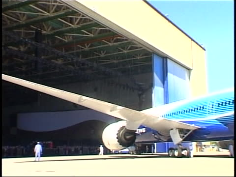 vídeos de stock, filmes e b-roll de spectators watch as the boeing 787 rolls out of the hangar during its debut at the boeing assembly plant in everett, washington state. - boeing 787