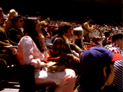 Spectators watch baseball game from stands near dugout at Candlestick Park / man gets up to leave walks up stairs another man follows Spectators...