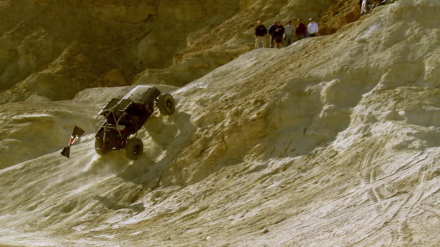 spectators watch from atop a hills as a jeep kicks up a lot of dust as it tries to climb a hillside. - off road racing stock videos and b-roll footage