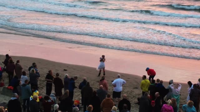 spectators watch naked bathers enter the water during the north east skinny dip at druridge bay in druridge englandpopular annual event which takes... - skinny dipping stock videos & royalty-free footage