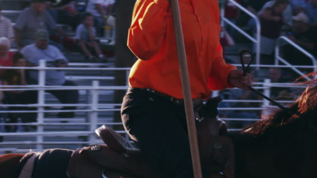 spectators watch riders with flags and horses perform a routine at a rodeo - shot in slow motion. - 1 minute or greater stock videos & royalty-free footage