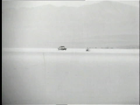 stockvideo's en b-roll-footage met spectators watching and taking photos / anson motors special speeding down the flats and setting new record - chrysler