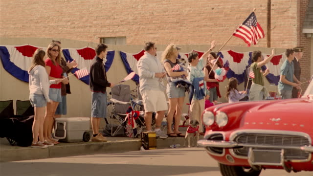 spectators watching parade from sidewalk waving and holding american flags as child beauty queen in red sports car drives down street in foreground / california - fourth of july stock videos & royalty-free footage