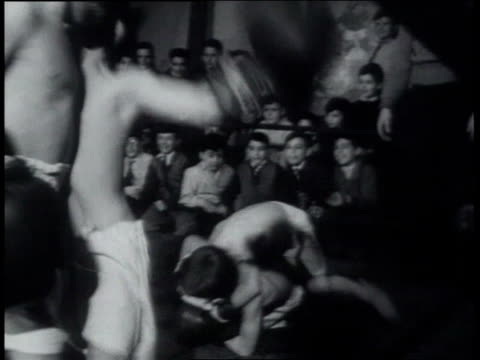 spectators watching ringside / boy boxer running away from one fight and into another the two falling on the mat / a spectator yelling ringside and... - blindfold stock videos & royalty-free footage