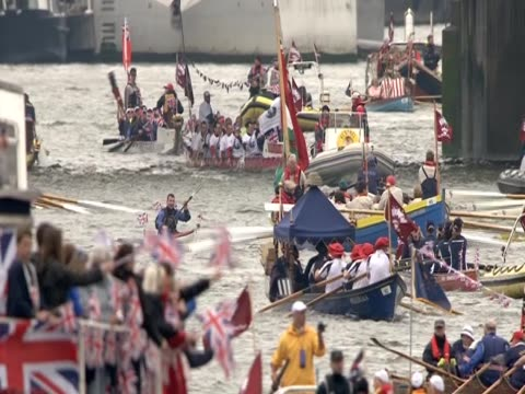 spectators waving flags as the diamond jubilee pageant travels along the river thames - beauty contest stock videos and b-roll footage