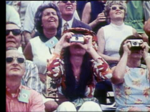 vidéos et rushes de spectators with cameras looking up at rocket launch / apollo 17 - 1972
