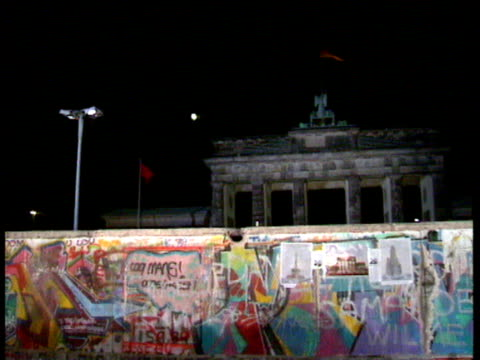 speculation that the brandenburg gate will open cu holes in the wall graffiti on wall east german guards at the gate fall of the berlin wall on... - 1989 bildbanksvideor och videomaterial från bakom kulisserna