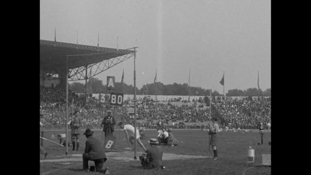 spedup footage of american pole vaulting with crowd and stadium beyond / slow motion view / [note film has nitrate deterioration] - 1924 stock videos and b-roll footage