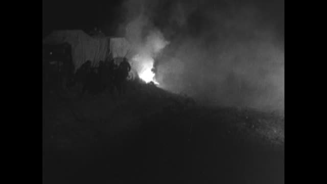 vidéos et rushes de [sped-up video] night: men in rain gear work with sandbags at levee near memphis / fire breaks out near tents and men rush to it / army trucks, with... - phare de véhicule