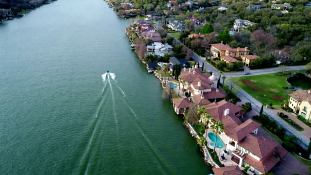 speed boat and mansions along the waters edge at town lake in austin , texas , usa at west lake - millionnaire stock videos and b-roll footage