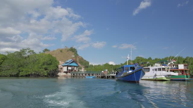 speed boat leaving from vellage on rinca island, komodo, indonesia - komodo island stock videos & royalty-free footage
